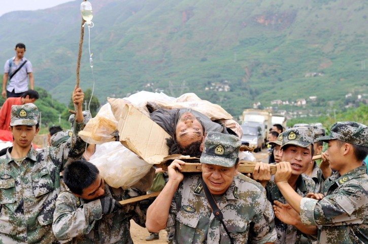 Rescuers carry an injured man during a rescue operation following Sunday's earthquake in Ludian county of Zhaotong city in southwest China's Yunnan Province, Monday, Aug. 4, 2014. Rescuers dug through shattered homes Monday looking for survivors of a strong earthquake in southern China's Yunnan province that killed hundreds and injured more than a thousand people. (AP Photo/Kyodo News) JAPAN OUT