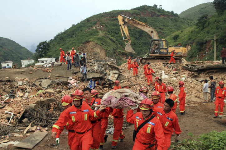 Rescue workers remove a dead body from the remains of a collapsed building at the epicenter of an earthquake that struck the town of Longtoushan in Ludian county in southwest China's Yunnan province Monday, Aug. 4, 2014.  Rescuers dug through shattered homes Monday looking for survivors of a strong earthquake in southern China's Yunnan province that toppled thousands of homes on Sunday, killing hundreds and injuring more than a thousand people. (AP Photo)