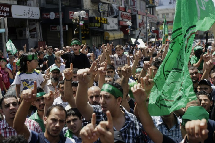 Hamas supporters shout slogans to support people in Gaza and Palestinian negotiators in Cairo, Egypt, during a demonstration in the West Bank city of Nablus on Friday, Aug. 15, 2014.  AP
