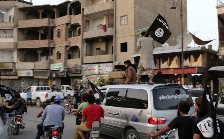 FILE - Members loyal to the Islamic State in Iraq and the Levant (ISIL) wave ISIL flags as they drive around Raqqa June 29, 2014.  Reuters