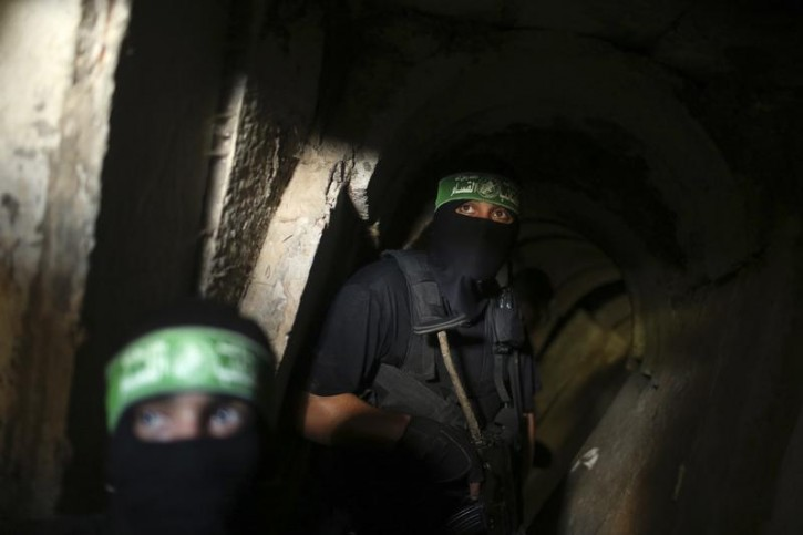 Palestinian fighters from the Izz el-Deen al-Qassam Brigades, the armed wing of the Hamas movement, are seen inside an underground tunnel in Gaza August 18, 2014. A rare tour that Hamas granted to a Reuters reporter, photographer and cameraman appeared to be an attempt to dispute Israel's claim that it had demolished all of the Islamist group's border infiltration tunnels in the Gaza war. Picture taken August 18, 2014. REUTERS/Mohammed Salem