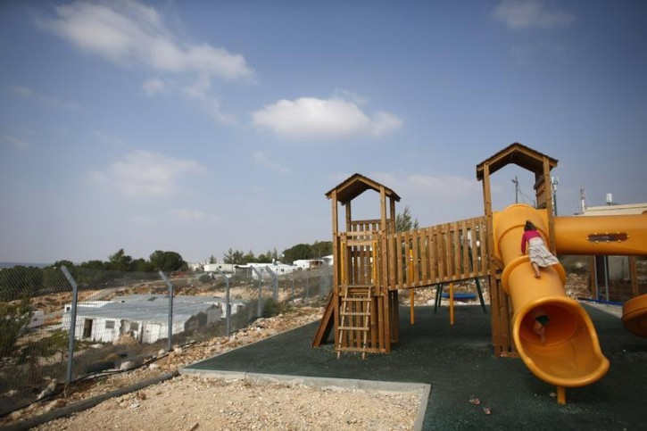 Children climb on a slide at a playground in a Jewish settlement in the Etzion settlement bloc, near Bethlehem August 31, 2014.  Reuters
