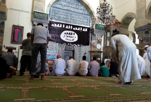 FILE - Worshipers pray at the Al-Noori Al-Kabeer mosque, next to flag used by the Islamic State (IS), in Mosul city, northern Iraq, 09 July 2014.  EPA