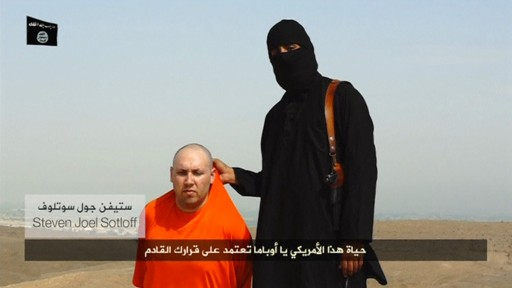 A masked Islamic State militant speaks next to U.S. journalist Steven Sotloff in this still image video posted on a social media website. REUTERS/Social Media Website via REUTERS TV