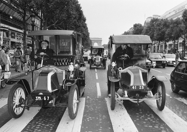 FILE - In this Sept. 8, 1984 file photo, three old motorized cabs dating back from World War I roll down the Champs-Elysees in Paris. Weeks after World War I erupted, with the capital under threat from German invaders, French military chiefs devised a novel way for soldiers to travel to the front lines: by taxi. To that end, they requisitioned hundreds of cabs, and their drivers were charged with the risky mission of getting thousands of troops to the battlefield. (AP Photo, File)