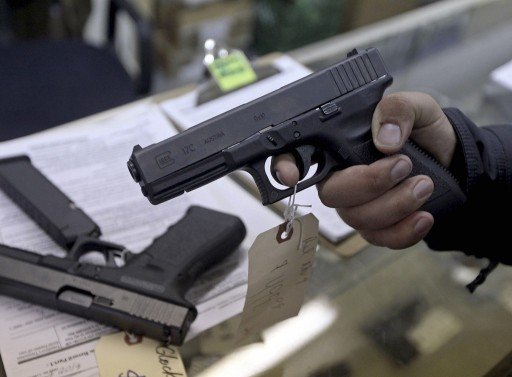PHOTO: A customer looks over a Glock 17 9mm hand gun at the Guns-R-Us gun shop in Phoenix, Arizona, December 20, 2012. REUTERS/Ralph D. Freso
