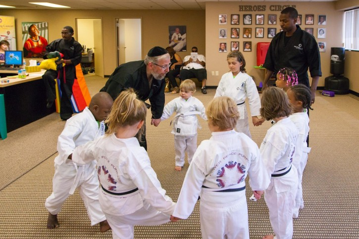 In this Sept. 22, 2014 photo Rabbi Elimelech Goldberg is seen with cancer stricken children teaching them pain management techniques. (Courtesy)