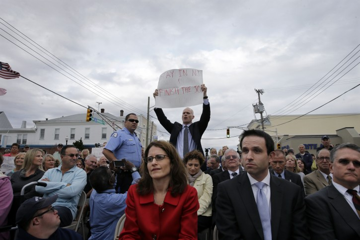 "Jim Keady holds up a sign and shouts at New Jersey Gov. Chris Christie during a event marking the second anniversary of Superstorm Sandy Wednesday, Oct. 29, 2014, in Belmar, N.J. Keady began heckling Christie about the pace of storm recovery and repeatedly interrupted the governor. After trying to brush the man off, Christie yelled back the man didn't know what he was talking about and was just showing off for the news cameras. When heckler Keady continued, Christie told him: ""Sit down and shut up. (AP Photo/Mel Evans)"