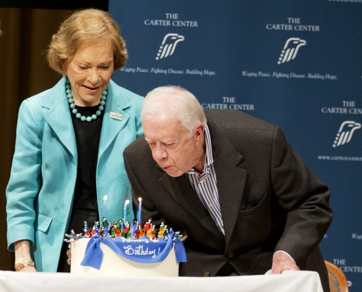 Former President Jimmy Carter, right, blows out candles on a birthday cake as wife Rosalynn looks on during his 90th birthday celebration, Wednesday, Oct. 1, 2014, in Atlanta. (AP Photo/David Goldman)
