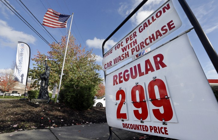 In this Wednesday, Oct. 29, 2014 photo, an American flag flies at a gas station advertising a discounted price for gas at $2.99 per gallon, with the purchase of a car wash, in Lynnwood, Wash. The U.S. is on track for the lowest annual average gas price since 2010 _ and the 2015 average is expected to be lower even still. (AP Photo/Elaine Thompson)