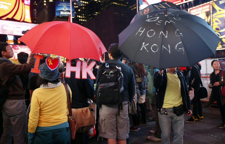 People hold up customized umbrellas during a rally in New York's Times Square, Wednesday, Oct. 1, 2014. Students bearing umbrellas as a sign of solidarity gathered at rallies in several U.S. cities to show support for pro-democracy protesters in Hong Kong. (AP Photo/Kathy Willens)