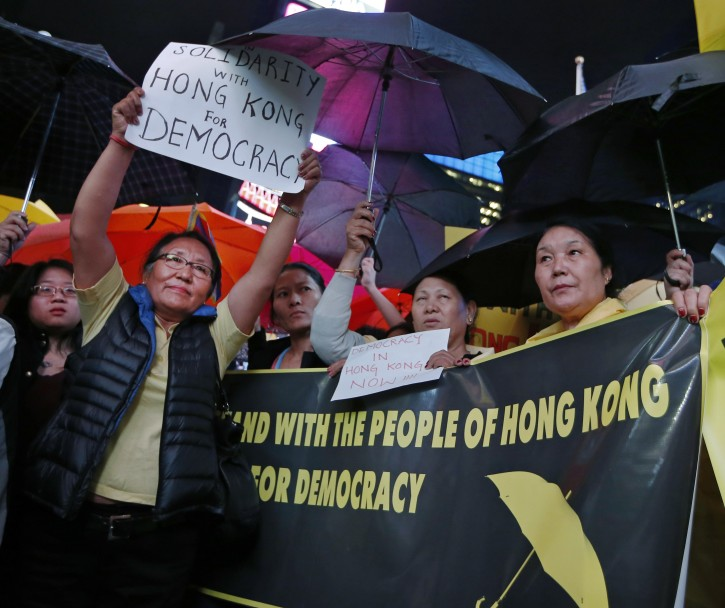 People show their solidarity with Hong Kong protesters during a rally Wednesday, Oct. 1, 2014, in New York's Times Square. The New York protesters called for a stop to violent police repression of democracy activists currently occupying central areas of the Chinese city.  Their umbrellas show solidarity with Hong Kong activists who use them as protection from tear gas. (AP Photo/Kathy Willens)
