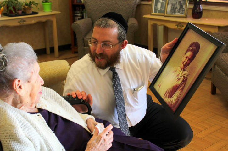 Oct. 30, 2014  -Mr. Moishe Heller of Grandell Rehab & Nursing Center shows Goldie a photo of herself on her 114th Birthday. Credits: Roy Renna / BMR Breaking News