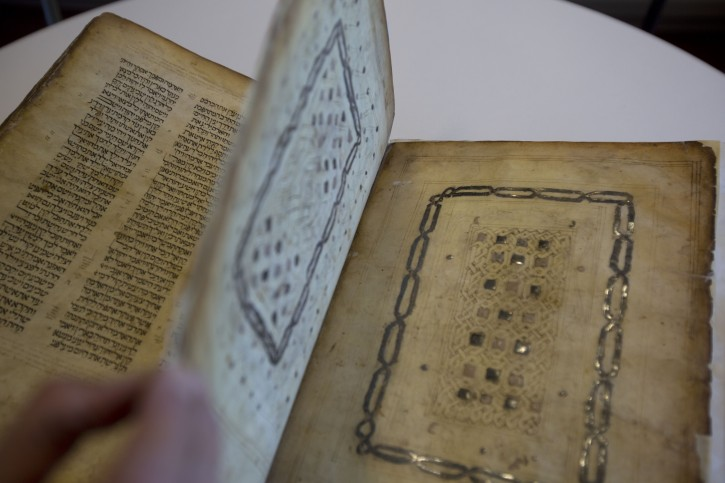 In this photo taken Sunday, Oct. 5, 2014, a library official shows a Jewish manuscript smuggled into Israel from Damascus in a Mossad spy operation in the early 1990s in Jerusalem. The manuscript is one of the earliest existing complete manuscripts of the Hebrew bible. This week, Israel's National Library in Jerusalem gave The Associated Press a rare peek at a selection of rare historical manuscripts in its collection. (AP Photo/Sebastian Scheiner)