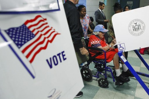 FILE - A voter sits in a wheelchair at a booth to fill out a ballot during the Democratic primary election in New York June 24, 2014.  REUTERS/Eduardo Munoz