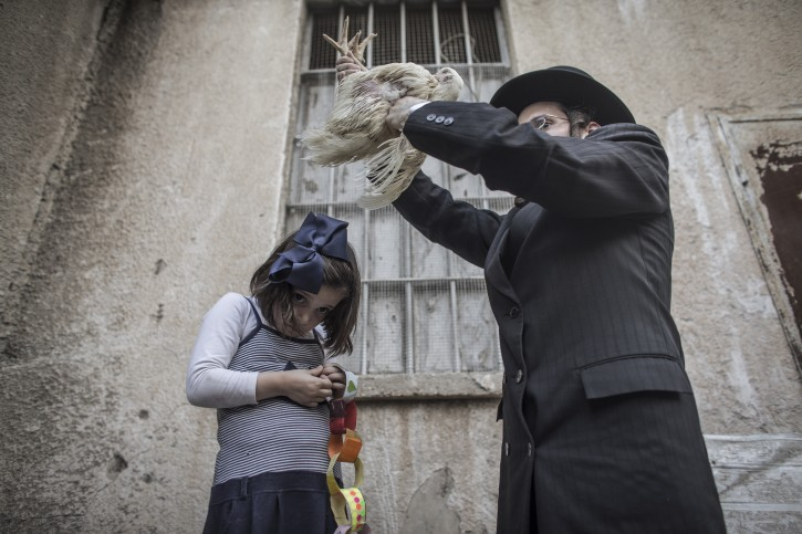 An ultra-Orthodox Jewish man swings a live chicken over the head of his daughter while reciting prayers for the 'Kaparot' ritual in Bnei Brak, outside Tel Aviv, 01 October 2014. EPA
