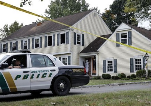 A Montgomery Township police officer sits in front of a partially burned home on Meadow Run Drive early Monday, Sept. 29, 2014, in Montgomery Township, N.J. John Sheridan, 72, the president of a major southern New Jersey hospital, and his 69-year-old wife, Joyce were killed when a fire broke out in their home, authorities said Sunday.(AP Photo/Mel Evans)