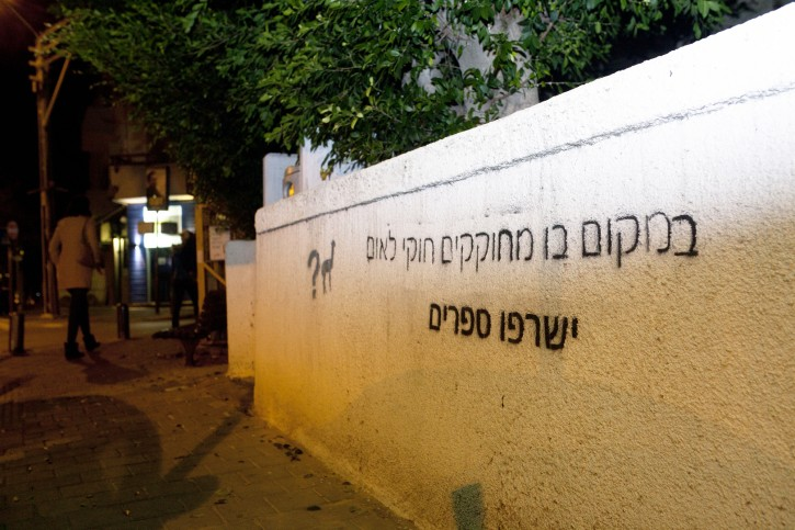 "Graffiti reading, ""where they legislate a Jewish state law people will burn books,"" seen sprayed on the exterior wall of a synagogue in central Tel Aviv on November 30, 2014. Photo by Amir Levy/Flash90"