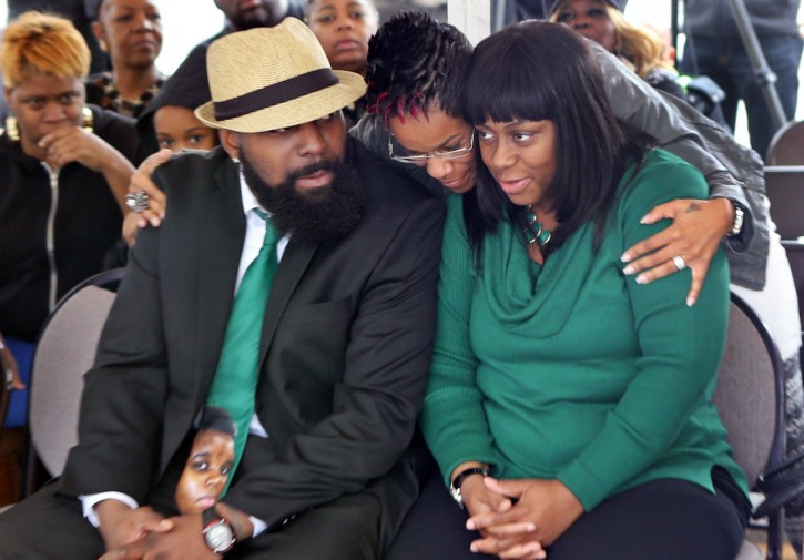 Michael Brown Sr., left, and his wife, Calvina Brown, right, are embraced by Trina Moorehead, of Florissant, upon their arrival at the Flood Christian Church service that was held in a tent on Sunday, Nov. 30, 2014, in Country Club Hills, Mo. The church was among dozens of businesses damaged or destroyed by fires Monday night. (AP Photo/St. Louis Post-Dispatch, J.B. Forbes)