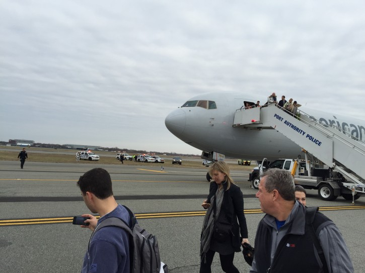 In a Sunday, Nov. 30, 2014 photo provided by Jacob Rosenberg, passengers deplane from American Airlines flight 67 after it landed at John F. Kennedy International Airport in New York, Sunday. Authorities at John F. Kennedy International Airport are investigating a bomb threat made to American Airlines Flight 67 from Barcelona that landed safely in New York City. (AP Photo/Jacob Rosenberg)