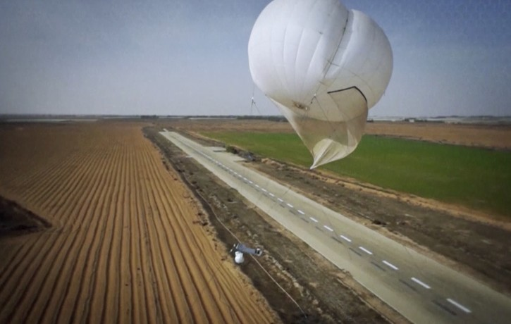 In this image made from undisclosed and undated video provided by RT LTA Systems Ltd. via AP video, a Skystar 180 aerostat system flies over land. The Israel-based RT LTA Systems Ltd. that makes the Skystar 180 aerostat system said the balloons can stay in the air for 72 hours and carry sensitive cameras meant to assist security forces in their daily work. (AP Photo/RT LTA Systems Ltd. via AP video)