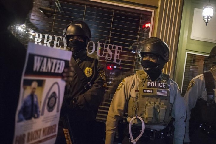 Protesters holding an image of officer Darren Wilson walk past police guarding a business in Ferguson, Missouri, November 29, 2014.  REUTERS