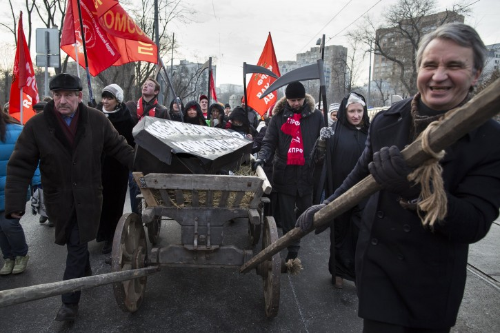 "Protesters pull a cart with a symbolic coffin with the words reading ""I did not have room in the hospital"" as they march in a street in Moscow, Russia, Sunday, Nov. 30, 2014.  At least 5,000 Russians marched on a frosty Sunday afternoon to protest plans to lay off thousands of doctors and close hospitals in Moscow against the backdrop of a flagging economy. The previous doctors' rally early this month was the first social protest in the country in a decade. The pressure on the Russian budget has intensified as the economy is taking a hit from low oil prices, a drop in the national currency and Western sanctions.(AP Photo/Alexander Zemlianichenko)"