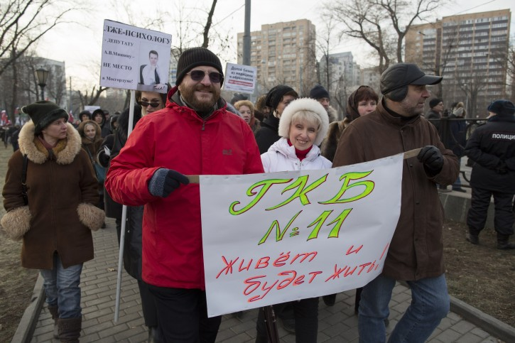"""Dr. Semyon Galperin, foreground left, and Olga Demicheva, in white, carry a poster reading """" The Hospital 11 lives and will live!"""" during a march in Moscow, Russia, Sunday, Nov. 30, 2014. AP"""
