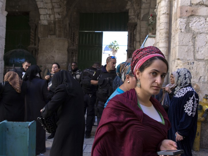 A right-wing Jewish woman passes a group of Palestinian women who want to enter the Hareem el-Sharif (The Noble Sanctuary) as police check their identity cards in Jerusalem's Old City, 06 November 2014. EPA