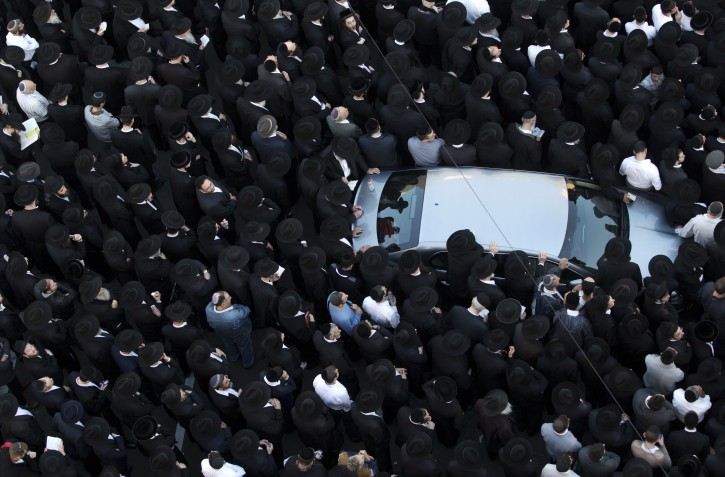 Ultra-Orthodox Jews gather and pray outside the yeshiva and synagogue where four Jews were slain by two Palestinians in the Har Nof religious neighborhood in jerusalem, 18 November 2014. EPA