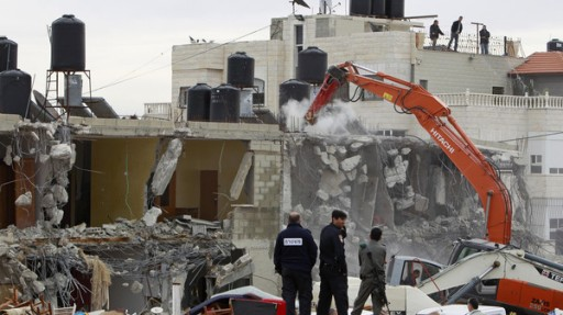 Israeli police officers look as an excavator demolishes a house in the East Jerusalem neighbourhood of Beit Hanina. (File photo: Reuters)