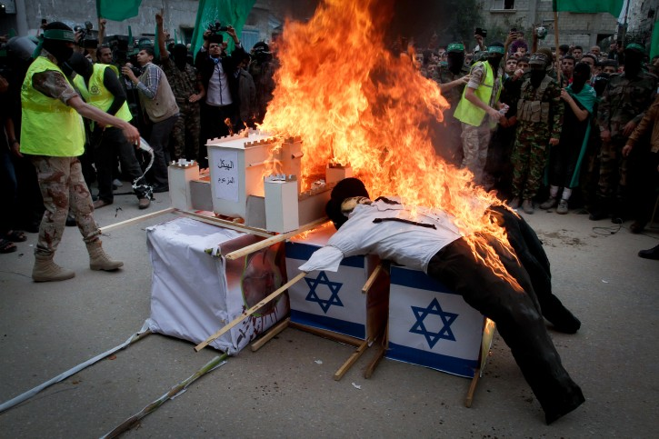 Palestinian militants from the Ezzedine al-Qassam brigade burn symbolic coffins with Israeli flags and effigies depicting Israeli settlers during a rally to commemorate the 27th anniversary of the Islamist movement's creation, at the Nuseirat refugee camp in the Central Gaza Strip on December 14, 2014. Photo by Abed Rahim Khatib/ Flash90