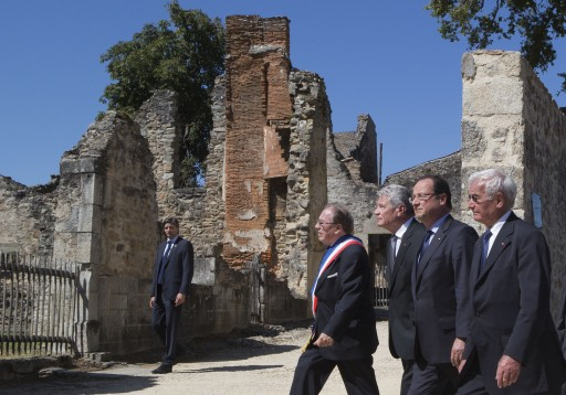 FILE - From left, Mayor of Oradour-sur-Glane, Raymond Fugier, German President Joachim Gauck, French President Francois Hollande and Robert Hebras, one of the two survivors still alive, walk through the ghost city of Oradour-sur-Glane, southwestern France, where on June 10, 1944, the Nazis massacred 642 civilians. (AP Photo/Michel Euler, Pool, File)