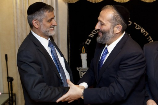 File photo of Eli Yishai (L) and Former Shas party Chairman Aryeh Deri (R) shaking hands. EPA/ABIR SULTAN