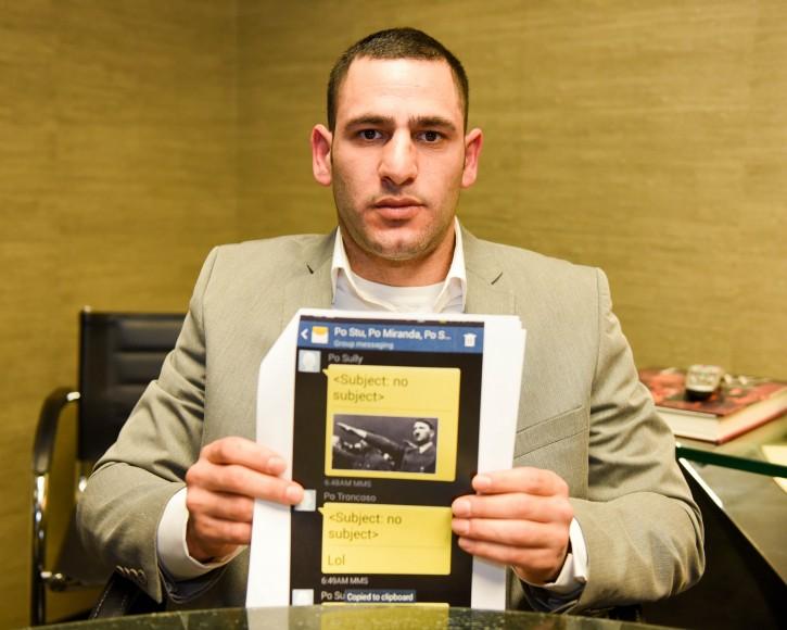 Former NYPD Officer, David Attali holds up one of many anti-semitic texts at his attorney's office in Lake Success Tuesday afternoon. Atali faced harassing text messages and notes on his locker at World Trade Center Police Command because he is Jewish. Atali, an ex-NYPD cop claims he was subject to such virulent attacks on his Jewish faith by fellow cops. (Courtesy NY Daily News)