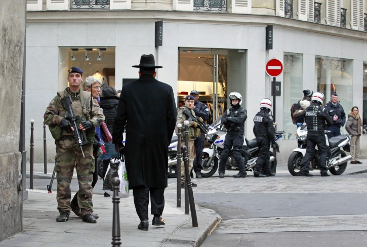 Police officers and French army soldiers patrol Rue des Rosiers street,  in the heart of Paris Jewish quarter, in Paris, Monday Jan. 12, 2015. (AP Photo/Remy de la Mauviniere)