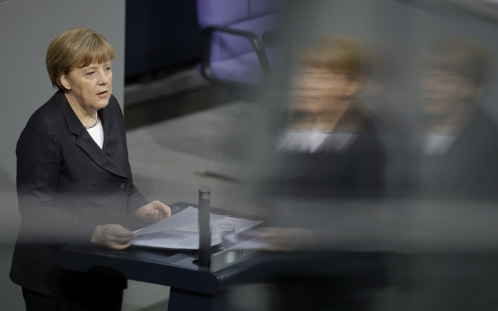 German Chancellor Angela Merkel is reflected in a window of the visitors' tribune as she speaks during a meeting of the German federal parliament, Bundestag, in Berlin, Germany, Thursday, Jan. 15, 2015. (AP Photo/Michael Sohn)