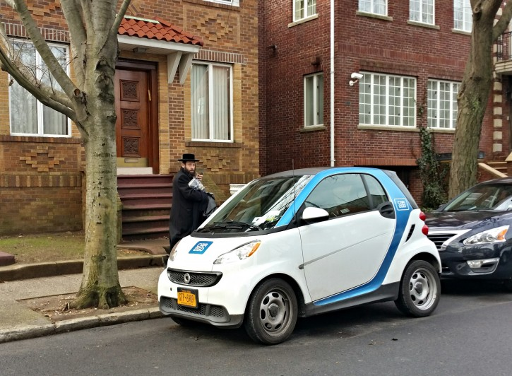 FILE - A Charedi man is seen passing by car sharing car2go on the streets of Borough Park on Jan. 19, 2014 (Eli Wohl/VINnews)