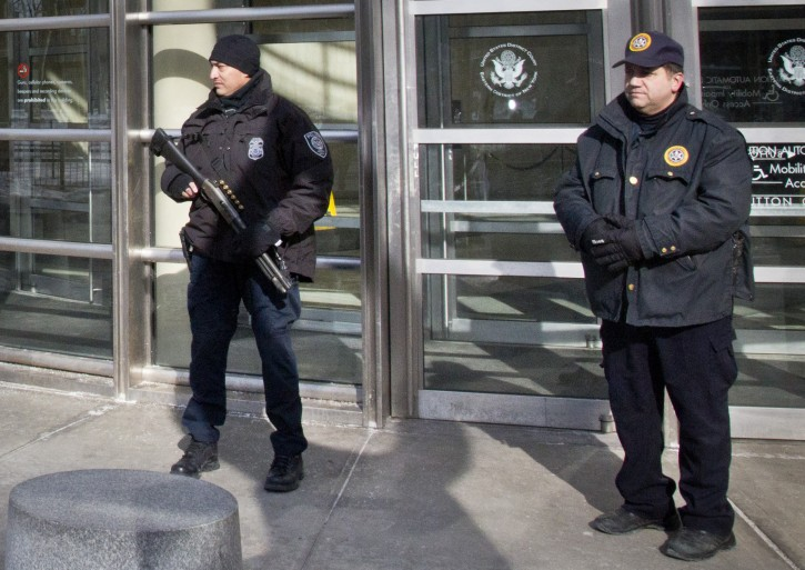 A Homeland Security police officer, left, joins a Federal Court policeman, right, as security is enhanced during the arraignment of two men on terrorism related charges, Wednesday, Feb. 25, 2015, in Brooklyn, N.Y. (AP Photo/Bebeto Matthews)