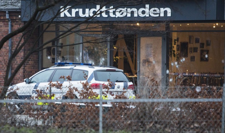 The scene outside the Copenhagen cafe, with bullet marked window, where a gunman opened fire Saturday, Feb. 14, 2015, in what is seen as a likely terror attack against a free speech event organized by an artist who had caricatured the Prophet Muhammad. The police believe there was only one shooter in the attack on a Copenhagen cafe that left one person dead and three police officers wounded during a free speech event. (AP Photo/Polfoto, Janus Engel)