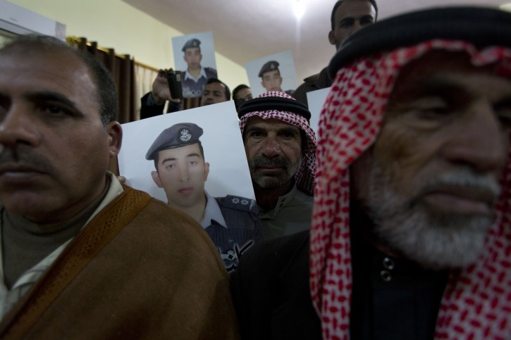 "Members of Al-Kaseasbeh, the tribe of Jordanian pilot, Lt. Muath al-Kaseasbeh, who is held by the Islamic State group militants, carry posters with his picture and Arabic that reads ""we are all Muath,"" at the captured pilot's tribal gathering divan, in his home town of Karak, Jordan, Saturday, Jan. 31, 2015.  AP"