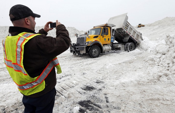 "Rick Chestnet, who works for the Pennsylvania Department of Transportation,  records a video on his cell phone as a department truck unloads snow at a ""snow farm"" in Boston, Saturday, Feb. 14, 2015. Crews from around the region have worked urgently to remove the massive amounts of snow that has clogged streets and triggered numerous roof collapses ahead of yet another winter storm due to arrive on Saturday. (AP Photo/Michael Dwyer)"