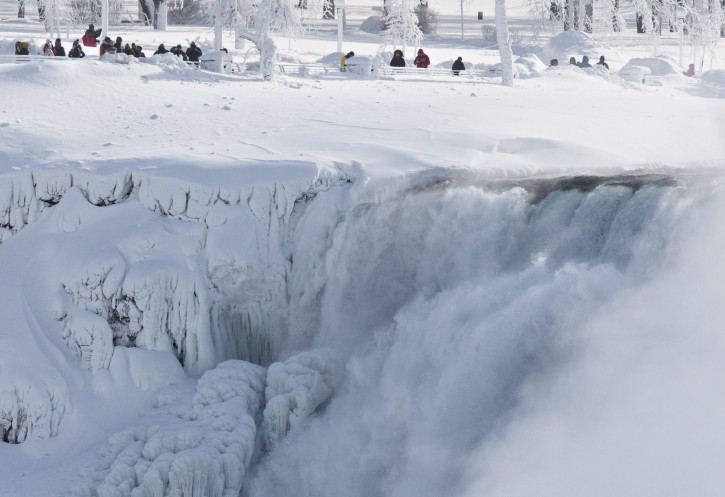 Niagara Falls State Park visitors look over masses of ice formed around the American Falls, photographed from across the Niagara River in Niagara Falls, Ontario, Canada, Thursday, Feb. 19, 2015. (AP Photo/The Canadian Press,Aaron Lynett)