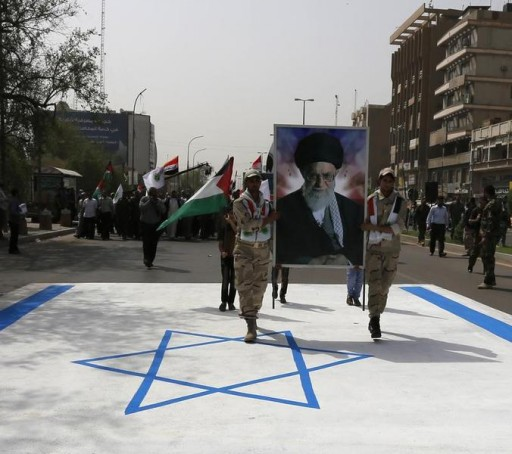 FILE - Iraqi Shiite Muslim men from Shi'ite Badr organisation hold a portrait of Iran's Supreme Leader Ayatollah Ali Khamenei as they walk along a street painted in the colours of the Israeli flag during a parade marking the annual al-Quds Day, or Jerusalem Day, on the last Friday of the Muslim holy month of Ramadan in Baghdad, July 25, 2014. REUTERS/Thaier al-Sudani