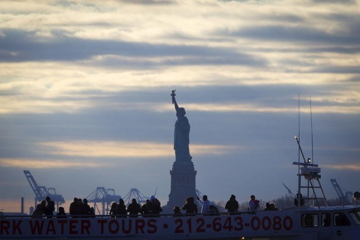 FILE - The Statue of Liberty is pictured behind a tourist boat in Battery Park in the Manhattan borough of New York, December 18, 2014. REUTERS/Carlo Allegri