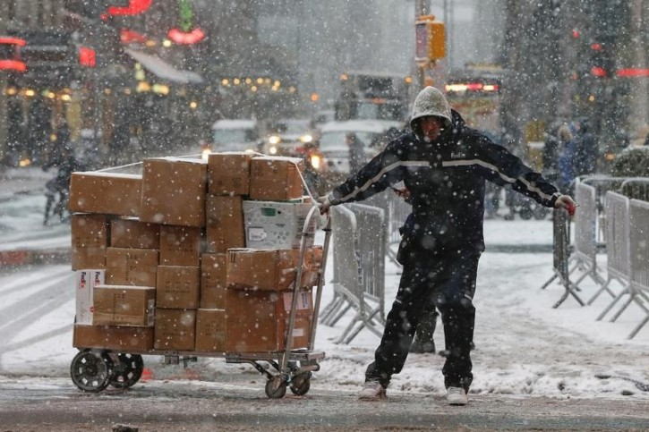 A FedEx delivery man pulls a trolley laden with packages along a snowy street at Times Square in New York February 2, 2015. REUTERS
