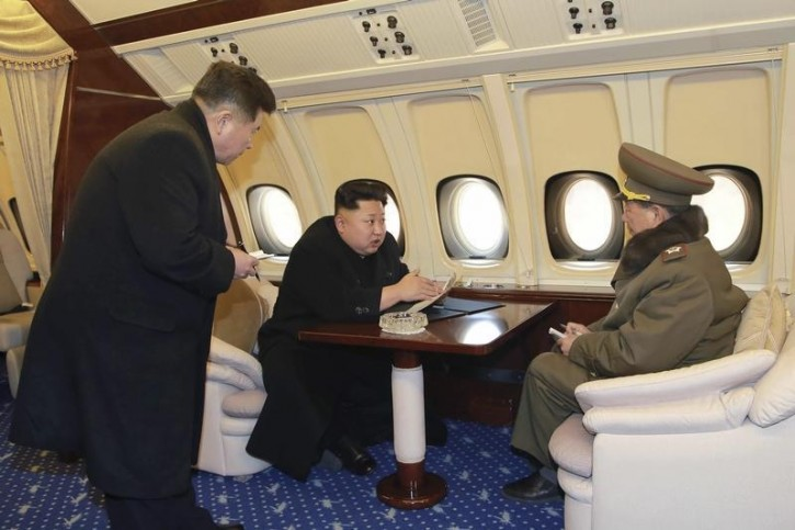 North Korean leader Kim Jong Un (C) talks with officials onboard his personal plane in this undated photo released by North Korea's Korean Central News Agency (KCNA) in Pyongyang February 15, 2015. REUTERS/