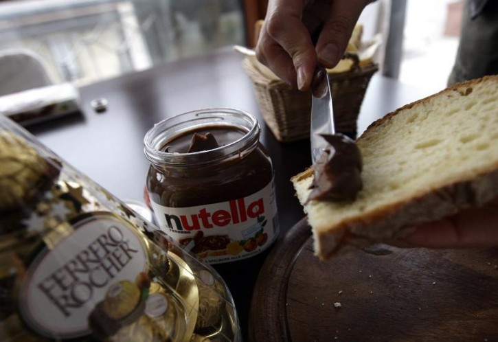 A woman spreads Nutella on a slice of bread in Milan.