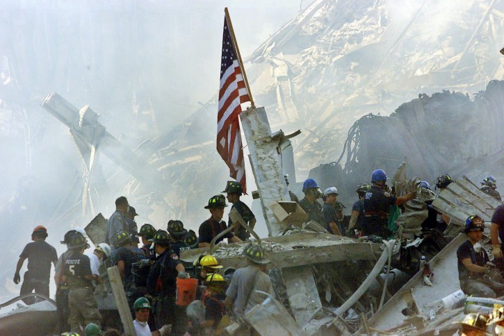 FILE - In this Sept. 13, 2001 file photo, an American flag flies over the rubble of the collapsed World Trade Center buildings in New York. For years, a handful of current and former American officials have been urging President Barrack Obama to release secret files that they believe document links between the government of Saudi Arabia and the terrorist attacks of September 11, 2001. Other officials, including the executive director of the 9-11 commission, have said the classified documents don't prove that the Saudi government knew about or financed the attacks_and that making them public would fuel bogus conspiracy theories.  (AP Photo/Beth A. Keiser, File)