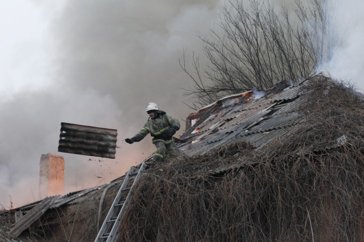 A firefighter dismantles a roof  to extinguish a building on fire after shelling between Russian-backed separatists and Ukrainian government in residential area of the town of  Artemivsk, Ukraine, Saturday, Feb. 14, 2015.  AP